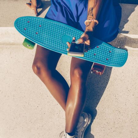 Outdoor lifestyle portrait of black young lady in bright outfit. Hipster girl sitting at skate park with blue penny shortboard skateboard and texting chatting on her phone. Swag, fashion. Sunny day.
