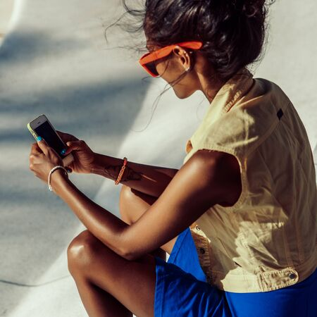 Outdoor lifestyle portrait of black young female in bright outfit and sunglasses. Hipster girl sitting at skate park with blue penny longboard skateboard and texting on the smartphone. Swag, fashion.