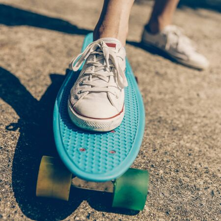Close up of feet of a beautiful woman in white sneakers rides on blue penny skateboard longboard with multicolored wheels. Urban scene, city life. Sport, fitness lifestyle. Cute hipster have fun. Фото со стока