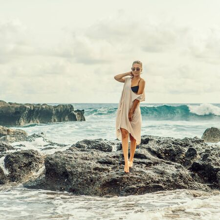 Pretty woman pose to camera in front of huge waves crashing on the rocks. Sexy lady on exotic beach seaside sunset or ocean sunrise. Danger, warning, travel, surfer relax and active lifestyle concept.