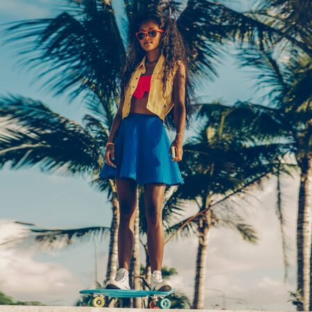 Outdoor lifestyle portrait of sporty black lady in bright outfit and sunglasses. Young hipster girl ride her penny skateboard in front of palm trees. She is happy. Sunny summer day. Swag, fashion. 免版税图像