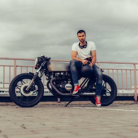 Rider guy with beard and mustache in red sneakers and black googles sit on classic style biker cafe racer motorcycle. Bike custom made in vintage garage. Brutal fun urban lifestyle. Outdoor portrait. 免版税图像