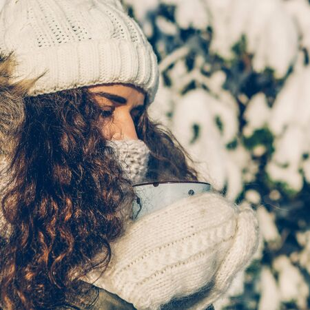 Portrait of a young beautiful girl in hipster white knitted mittens drink hot tea on a bright winter day. Close-up of a cup with hot liquid in hand. Trees in pure first snow on a background.
