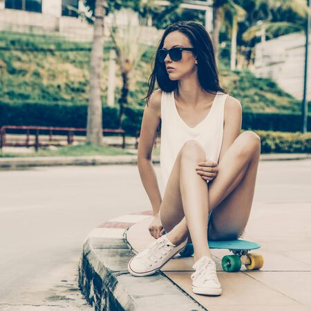 Portrait of slim young beautiful girl in white t-shirt, short jeans shorts and trendy sunglasses sit on blue penny skateboard. Urban scene, city life. Cute attractive sexy hipster woman have fun. 免版税图像