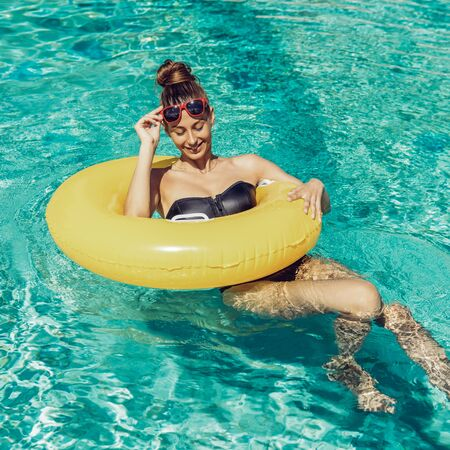 Amazing beautiful woman in black swimsuit correct trendy sunglasses and have fun at swimming pool party. Outdoor portrait of sexy girl enjoying hot holidays, swim with inflatable yellow ring.