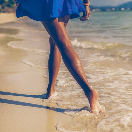 Outdoor lifestyle close-up of long beautiful legs of a sporty black teenage girl at tropical seashore. Closeup detail of female feet, water splash and golden sand. Young hipster, sunny hot summer day.