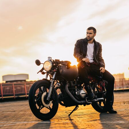 Handsome fit rider man with beard and mustache in black leather biker jacket sit on classic style cafe racer motorcycle at sunset time. Bike custom made in vintage garage. Brutal fun urban lifestyle.