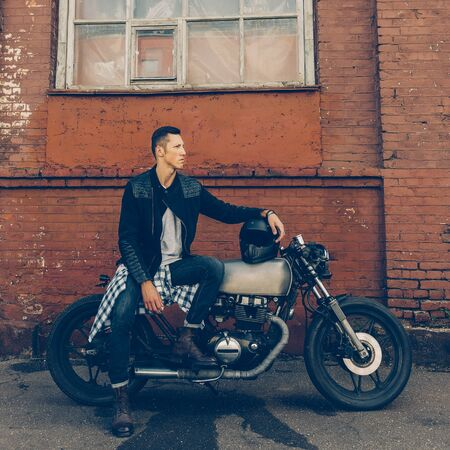 Handsome biker guy in black leather jacket sit on classic style cafe racer motorcycle and hold helmet on gas tank. Bike custom made in vintage garage. Brutal fun urban lifestyle. Outdoor portrait.