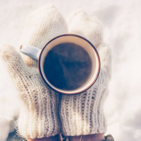 Fashion beautiful woman in hipster white knitted mittens drink hot tea on a bright winter day. Close-up of a cup with hot liquid in hand. Trees in pure first snow on a background. Top view.