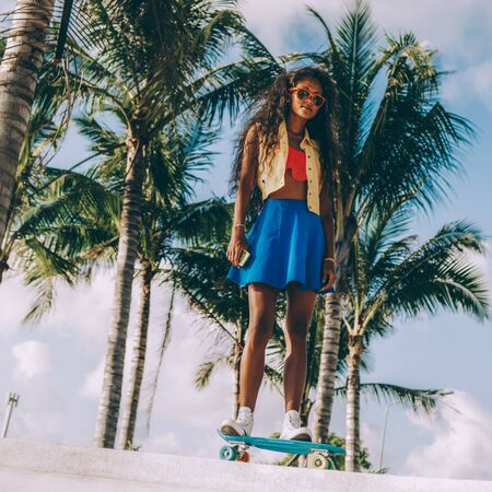 Outdoor lifestyle portrait of sporty black female in bright outfit and sunglasses. Young hipster girl ride her penny skateboard in front of palm trees. She is happy. Sunny summer day. Swag, fashion.
