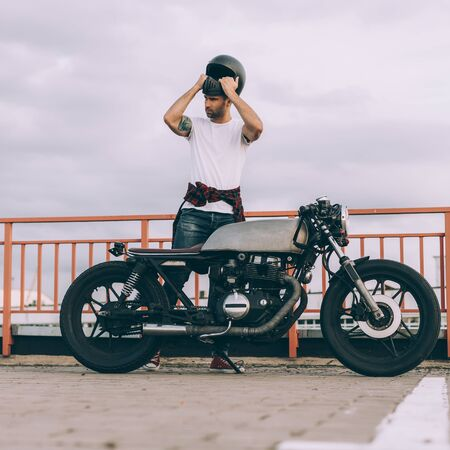 Handsome happy rider guy with beard and mustache put on black moto helmet and sit on his classic style biker cafe racer motorcycle. Bike custom made in vintage garage. Brutal fun urban lifestyle. 免版税图像