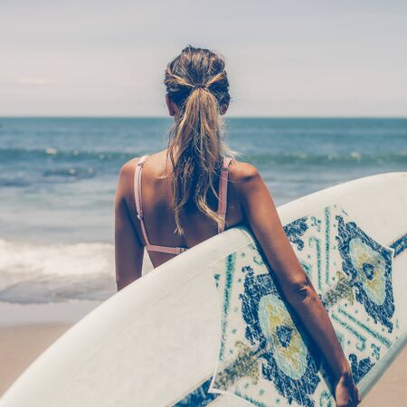 Beautiful young slim girl in sexy pink bikini with long custom surfing board single fin in front of blue ocean ready to surfing. Tropic island vacation. Summer travel girl, active hipster lifestyle. 免版税图像