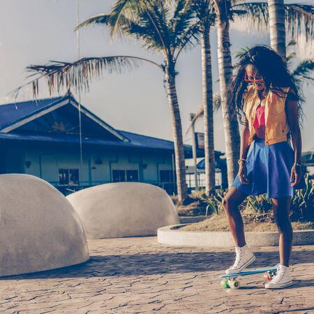 Outdoor lifestyle portrait of black young female in bright outfit and sunglasses. Young hipster girl try to ride her blue penny shortboard skateboard . She is happy. Sunny summer day. Swag, fashion. Фото со стока