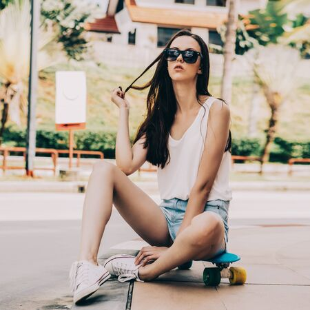 Portrait of sporty beautiful girl in white t-shirt, short jeans shorts and trendy sunglasses sit on blue penny skateboard. Urban scene, city life. Cute attractive sexy hipster woman correct her hairs. 免版税图像 - 127224998