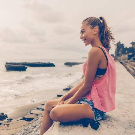 Pretty girl in sport summer outfit sit on pier and look forward to the future and smile. Sexy lady on sea beach sunset or ocean sunrise. Travel, explore, active yoga and meditation lifestyle concept.