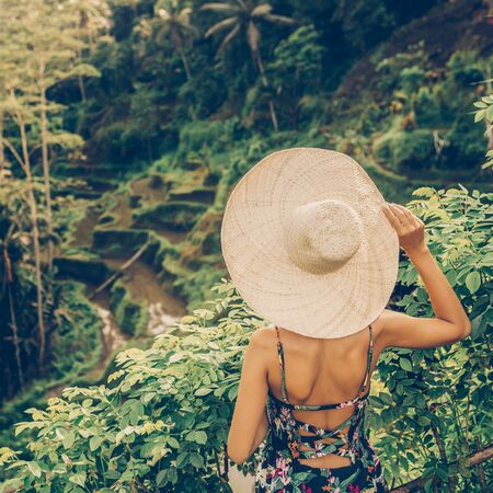 Beautiful young female in straw hat travel and explore world. Girl look at typical Asian hillside with rice farming, mountain shape green cascade rice field terraces paddies. Ubud, Bali, Indonesia.