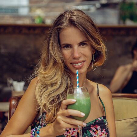 Beautiful young woman drink fresh green smoothie from glass in cafe. Healthy eating lifestyle concept, organic detox juice with spinach, celery and vegetable nutrition. Vegan meal, raw food diet.