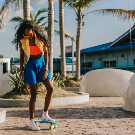 Outdoor lifestyle portrait of sporty black female in bright outfit and sunglasses. Young hipster girl try to ride her blue penny longboard skateboard. She is happy. Sunny summer day. Swag, fashion. Фото со стока
