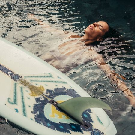 Beautiful young female in sexy bikini relax in pool with her longboard single fin surfing board under tropical rain. Girl travel and explore world. Travel and adventure mockup. Romantic scene concept. 免版税图像
