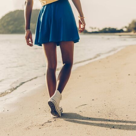 Beautiful sporty black  in blue skirt walk at tropical ocean shore with golden sand. Outdoor lifestyle close up of  long legs in white  sneakers. Sunny hot summer day. Swag, fashion. 免版税图像
