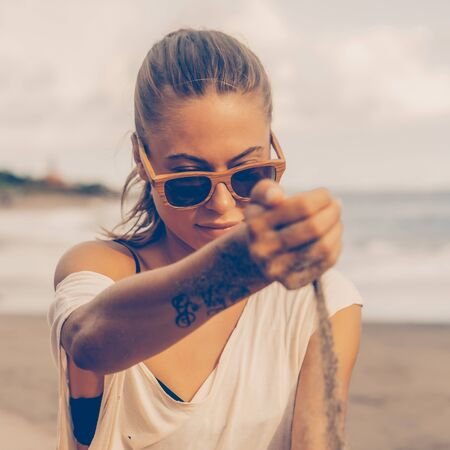 Pretty woman in casual clothes and wooden sunglasses look to the sand running through hand. Lady on sea beach sunset or ocean sunrise. Travel, explore, active yoga and meditation lifestyle concept.