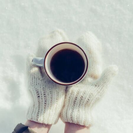 Young beautiful lady in hipster white knitted mittens drink hot tea on a bright winter day. Close-up of a cup with hot liquid in hand. Trees in pure first snow on a background. Top view.