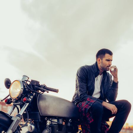 Handsome rider man with beard and mustache in biker jacket smoking and hold cigaret sit on classic style cafe racer motorbike at sunset. Bike custom made in vintage garage. Brutal fun urban lifestyle.