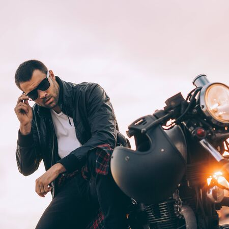 Handsome rider guy with beard and mustache in black biker jacket put on sunglasses sit on classic style cafe racer motorcycle at sunset. Bike custom made in vintage garage. Brutal fun urban lifestyle.