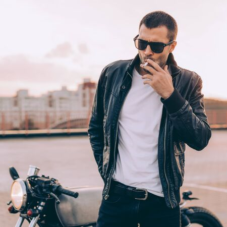 Beautiful happy rider man with beard and mustache in black biker jacket, jeans and fashion sunglasses smoking cigaret near classic style cafe racer motorbike at sunset. Brutal fun urban lifestyle.