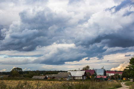 Storm clouds over the village. Beautiful menacing sky over the field and little village. Stock Photo