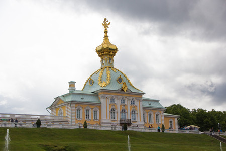 scepter: PETERHOF, SAINT-PETERSBURG, RUSSIA - JUNE 10, 2016: Armorial housing of the Grand Palace in Peterhof. Cloudy, rainy weather in Peterhof. Dome of the west wing of the palace, peterhof, with three headed eagle. Saint Petersburg, Russia.