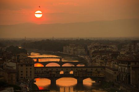 Blick auf den Arno und die berühmte Brücke Ponte Vecchio. Erstaunliches Abendlicht der goldenen Stunde. Schöner goldener Sonnenuntergang in Florenz, Italien. Standard-Bild