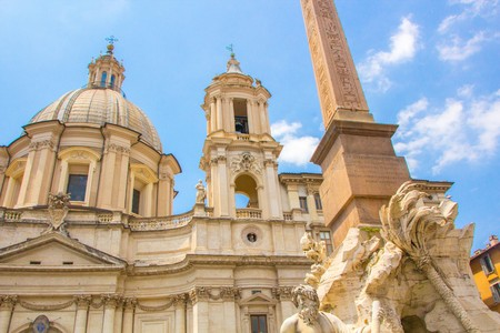 Fountain of the Four Rivers with an Egyptian obelisk and Sant Agnese Church on the famous Piazza Navona Square. Sunny summer day. Rome, Italy. Architecture and sights of Rome.