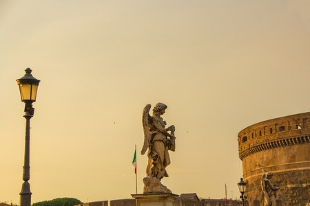 Statue angel on the bridge over the Tiber, near the Saint Angel Castle. Beautiful evening golden sunset at Saint Angel Castle. St. Angelo Bridge crossing the river Tiber, historical center of Rome. Editorial