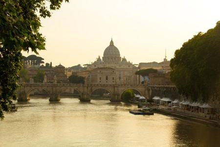Beautiful view of St. Peters Basilica in the Vatican from the Tiber River in Rome. St. Peters Basilica and Aelian Bridge across Tiber River in Rome, Italy.