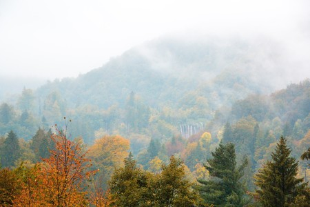 Plitvice lakes national Park, Croatia. Autumn landscape. Golden trees, fog, mountains and waterfall.