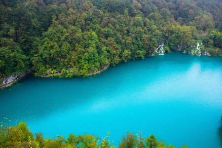 Top view of a large blue lake in Plitvice lakes national Park, Croatia. Beautiful landscape: clean blue water, forest, waterfalls. Amazing nature landscape, outdoor travel background.