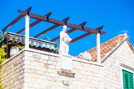 White statue of a man with a shiny iron stick on the roof of a house in the centre of the old town of Split, Croatia. Diocletian Palace. 版權商用圖片