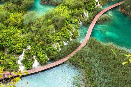 Park Narodowy Jezior Plitwickich, Chorwacja. Most chodnikowy nad stawem, który przechodzi przez niesamowite małe wodospady.