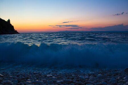 Beautiful sunset on the sea. Dramatic evening sea landscape. Waves beating against the shore, long exposure. Sunset beach.