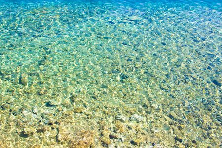Clear amazing azure coloured sea water. Transparent sea water with sunlight on pebbles. Sea water background.
