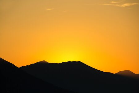 Sunset over the mountains. Golden hour. A silhouette of mountains and a golden sky lit by the last rays of the sun. Archivio Fotografico - 138047604