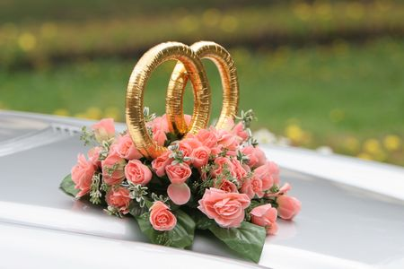 Wedding rings on the car with beautiful bunch of flowers photo