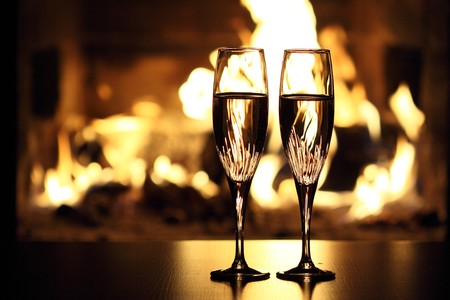 two glasses in front of fireplace Stock Photo