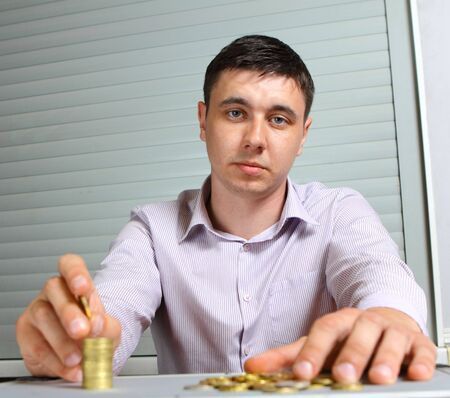businessman putting the coins in columns photo
