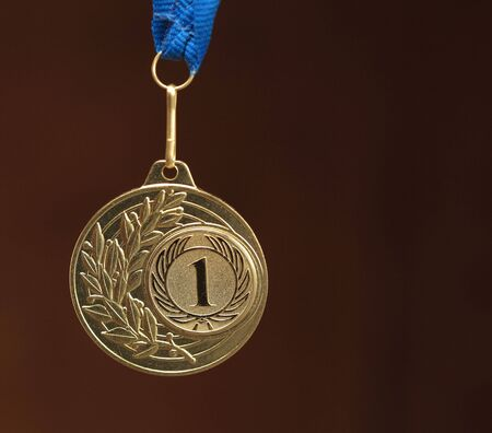 accolade: gold medal on brown background Stock Photo