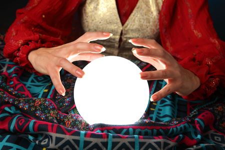 fortuneteller: hands of a fortune-teller working with a shining crystal ball