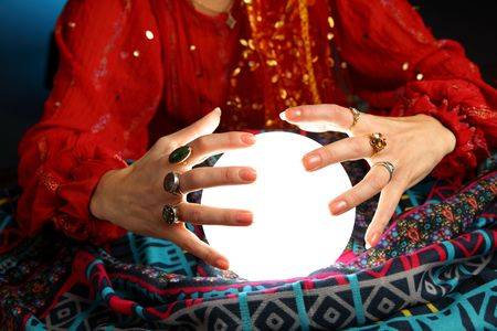 crystals: hands of a fortune-teller working with a shining crystal ball
