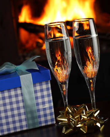 glasses with champagne with christmas entourage, fire as the background photo