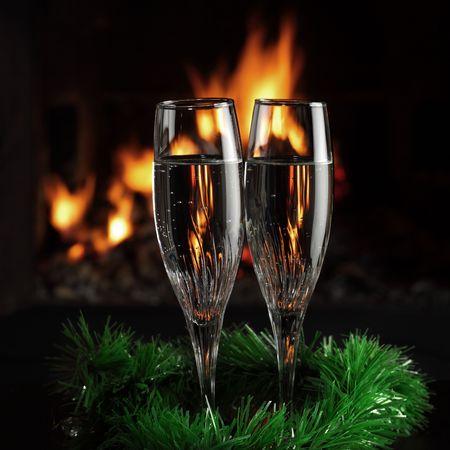 camino natale: occhiali con champagne con entourage di Natale, fuoco come sfondo